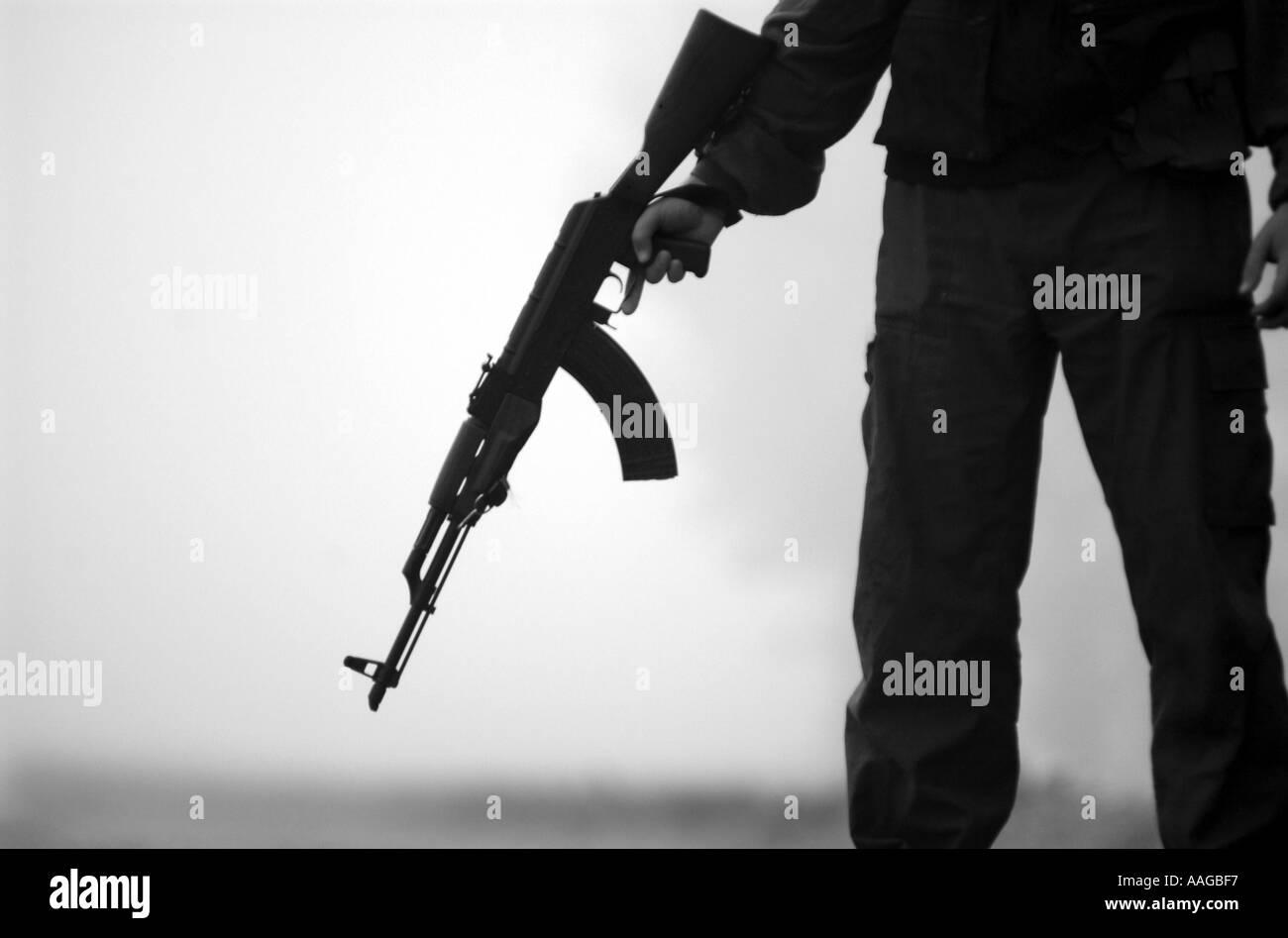 a terrorist dressed in a balaclava holding an AK47 kalashnikov rifle - Stock Image