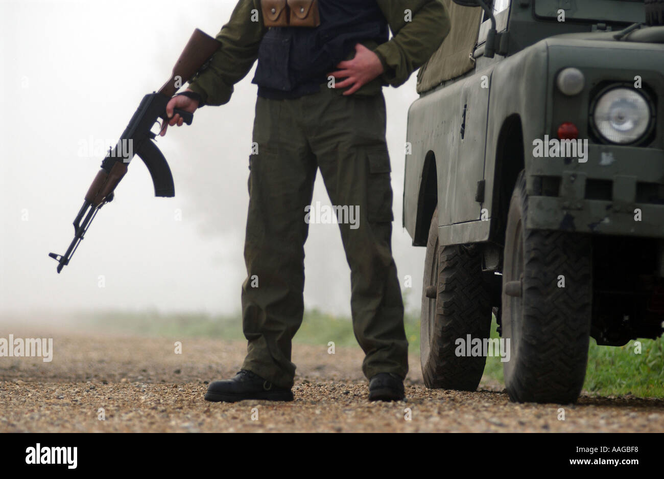 a terrorist dressed in a balaclava holding an AK47 kalashnikov rifle and wearing a belt of bullets next to a land rover - Stock Image