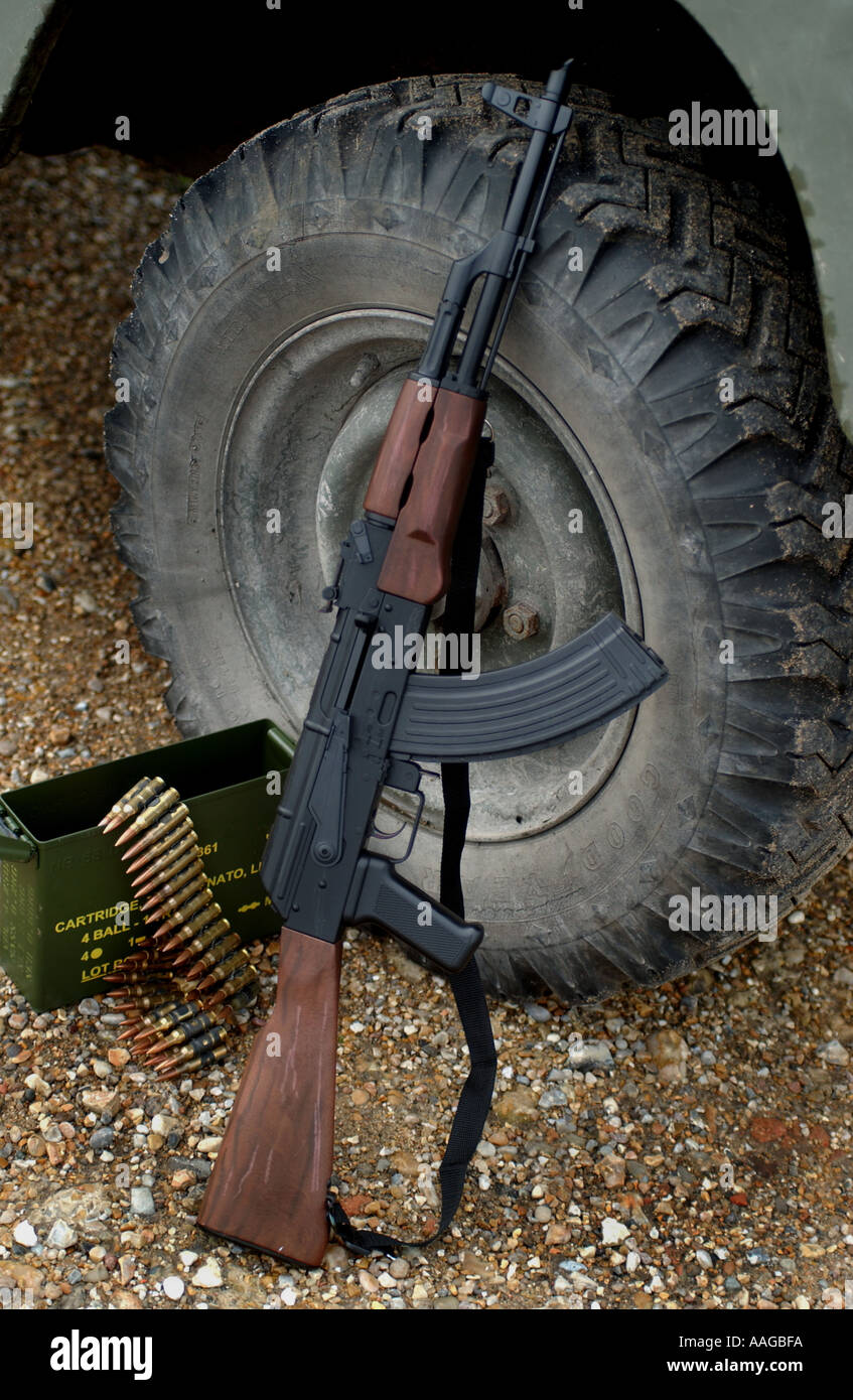 AK47 Kalashnikov rifle with ammunition box and a belt of bullets leaning against a land rover wheel - Stock Image