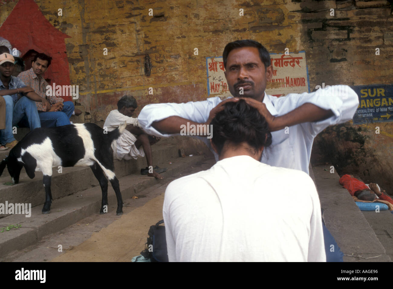 Man getting a massage at a ghat in Varanasi Uttar Pradesh India - Stock Image