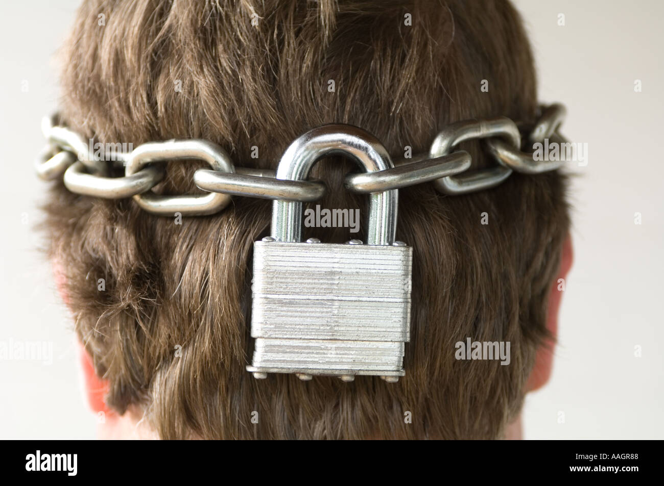 abstract view of male head enclosed in chain and padlock - Stock Image