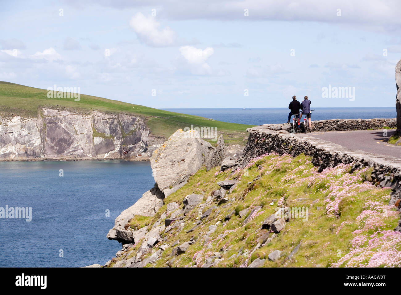 Ireland Kerry Dingle Peninsula Slea Head cyclists on coastal road looking to Dunmore Head - Stock Image