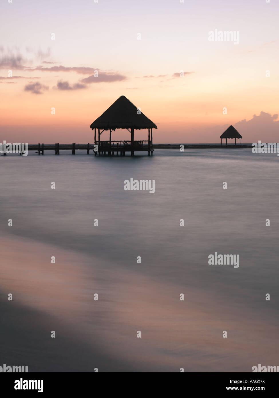 Mexico Quintana Roo Yucatan Peninsula Akumal Mayan Riviera pier with palapa jutting out to the water from the beach - Stock Image