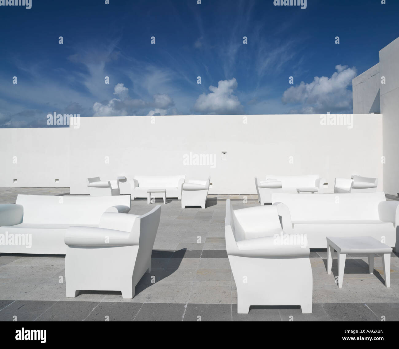 Mexico Quintana Roo Yucatan Peninsula Akumal Mayan Riviera white chairs and couches against a white wall and blue - Stock Image