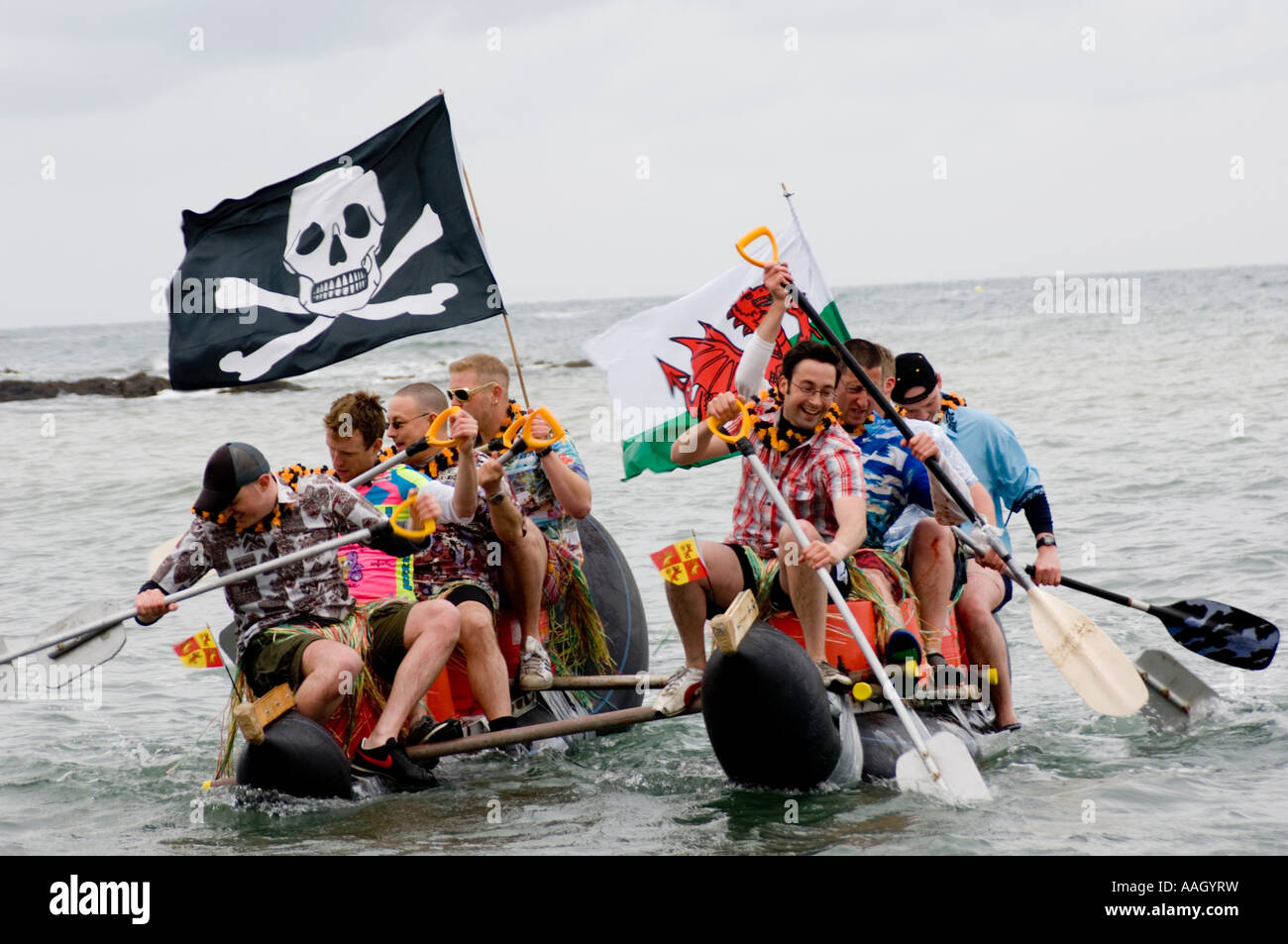 Group of men paddling a home made raft flying pirate flag and welsh banner in a charity race Aberystwyth Ceredigion, - Stock Image