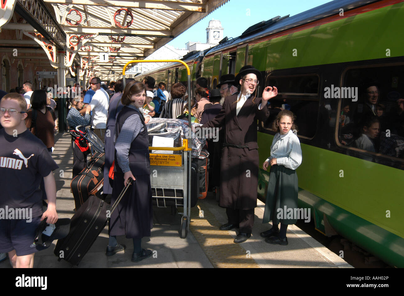 Families of orthodox hassidic jews on annual holiday in Aberystwyth railway station catching the train home to London - Stock Image