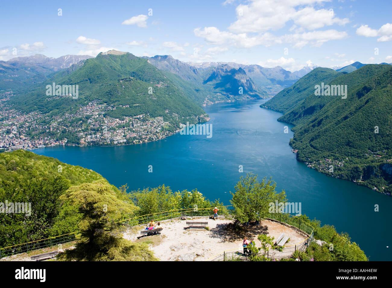 view from Monte San Salvatore 912 m over Lake Lugano and Lugano people resting on benches Lugano Ticino Switzerland Stock Photo