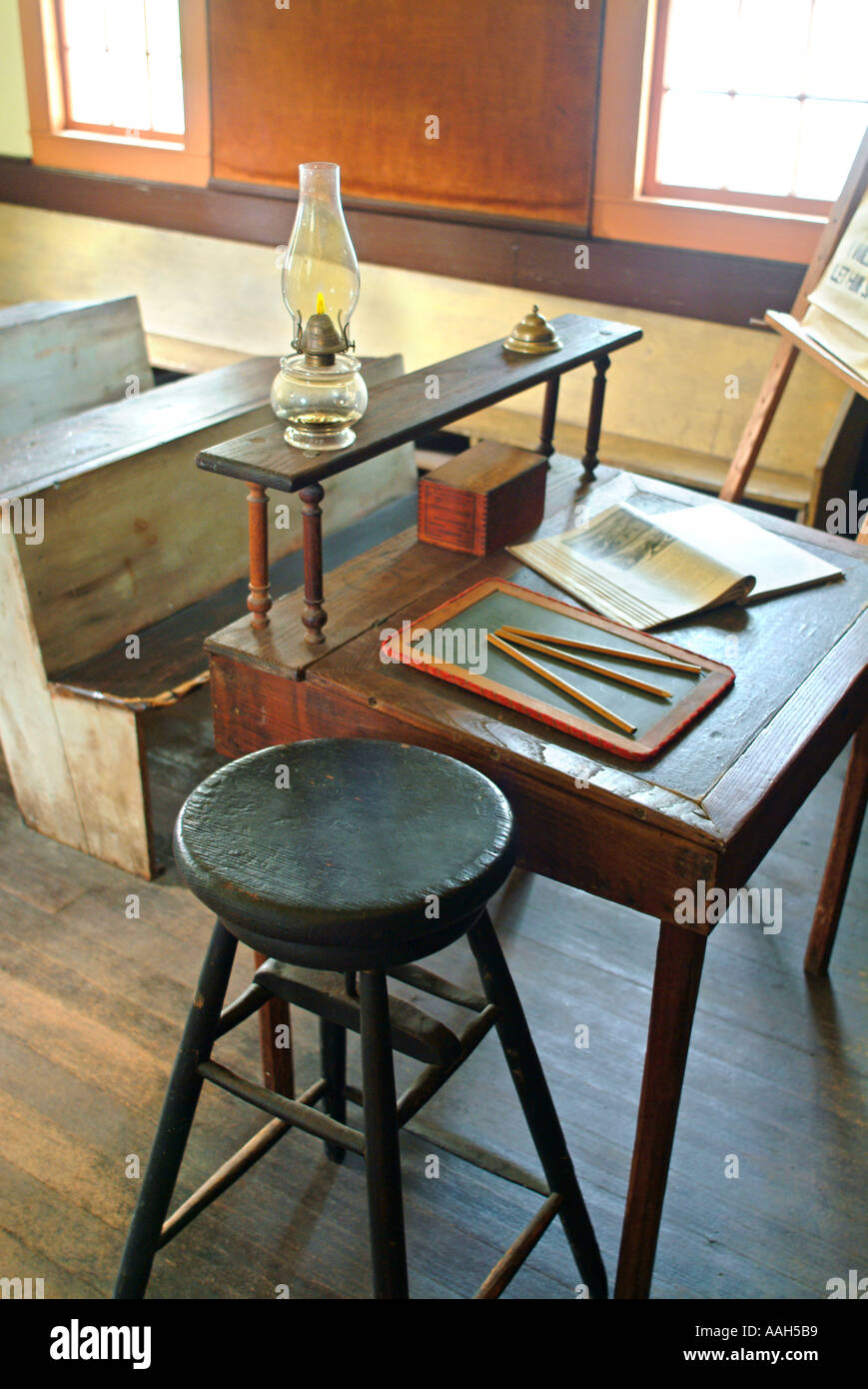old fashioned one room school house with wooden desk chairs stool
