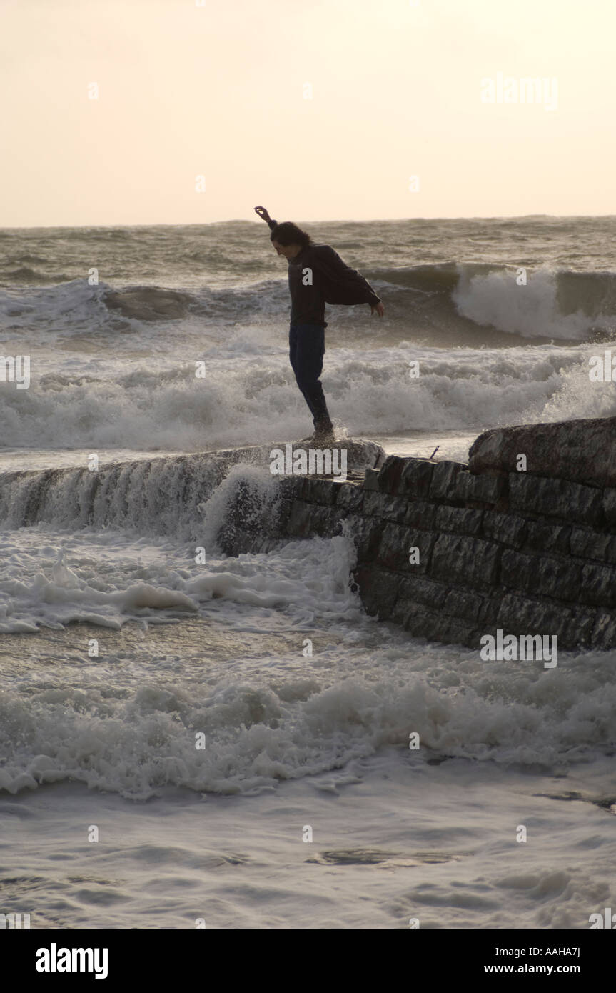 young man standing on stone jetty during a storm dodging the waves : health and safety risk, aberystwyth wales UK - Stock Image