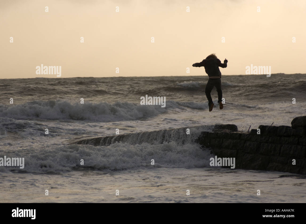 young man jumping on stone jetty during a storm dodging the waves: health and safety risk - Stock Image