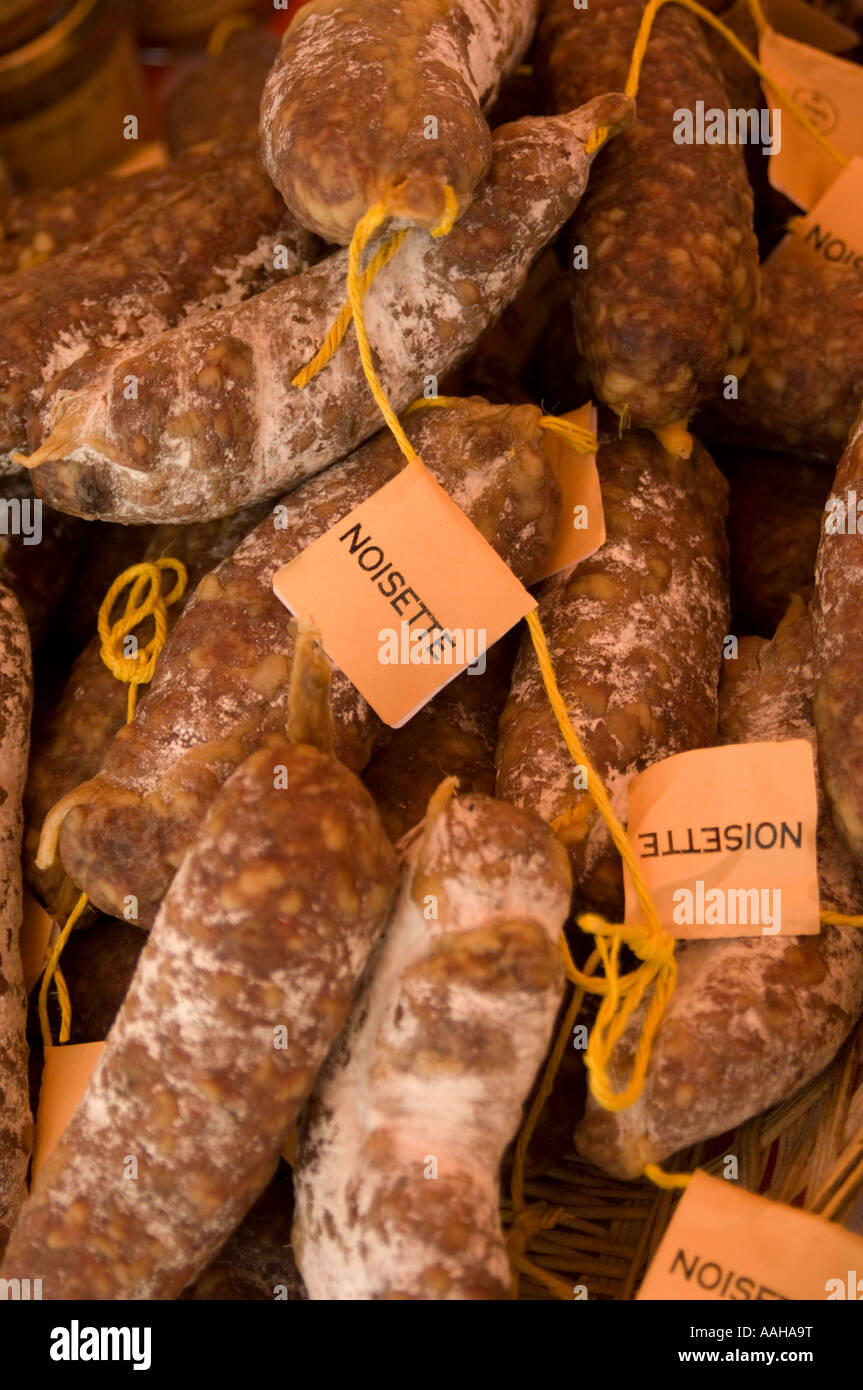 pile of strings of imported artisan dry French sausage Saucisson Sec noisette for sale on market stall, UK - Stock Image