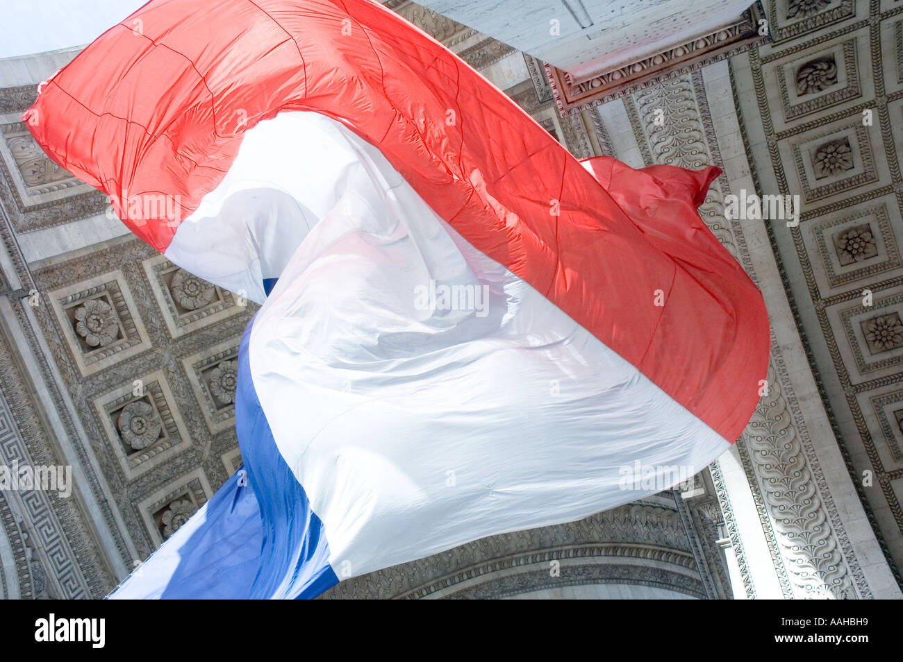 French tri-colour flies beneath the Arc de Triomphe in Paris, France - Stock Image