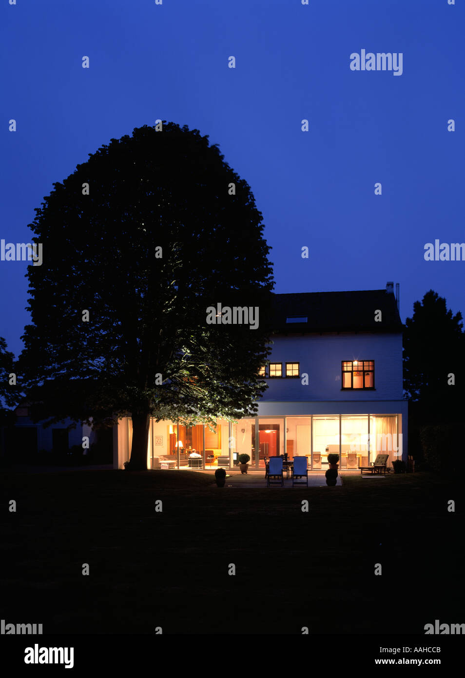 cottage country house with lime tree at dusk - Stock Image