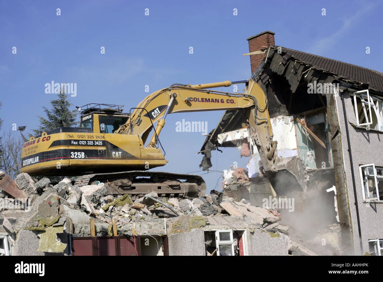A bulldozer demolishing old council houses in Ley Hill, Northfield, Birmingham, England. - Stock Image