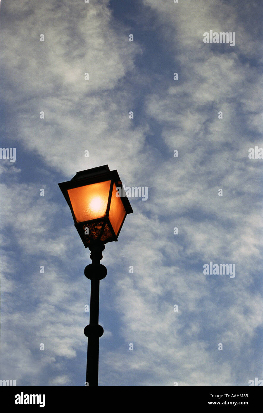 Lit Old Fashioned Lamp Post And Dramatic Sky