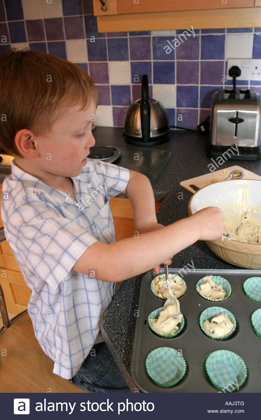 A young boy making fairy cakes in his mum's kitchen. - Stock Image