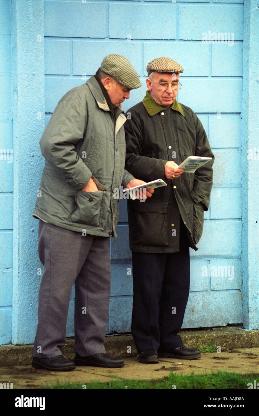 Two old men in flat caps read their programmes before a rugby match at  Resolven RFC South Wales UK 65f6316d2cd