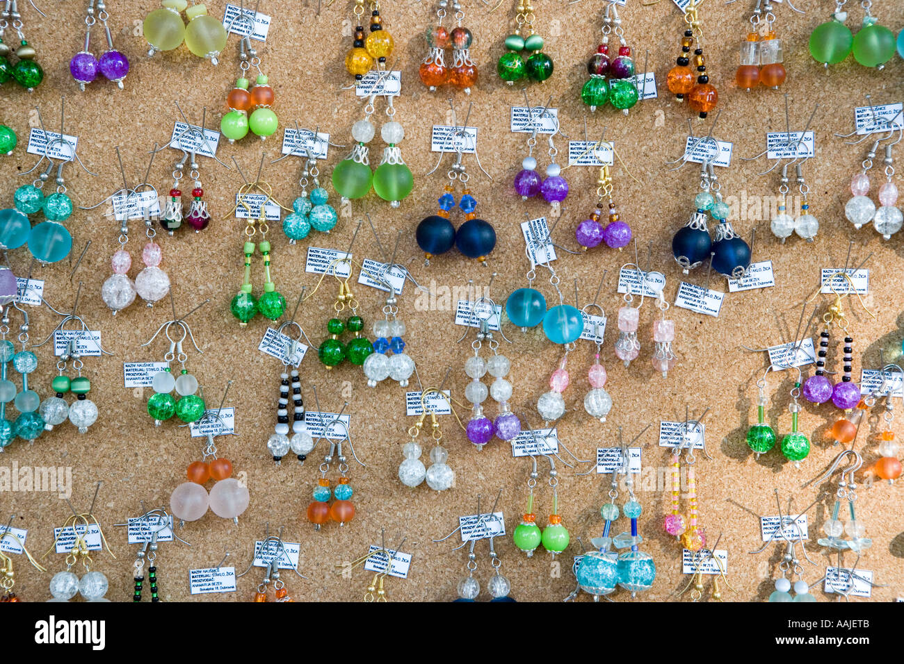 Brightly coloured Ear rings for sale pinned to a board - Stock Image