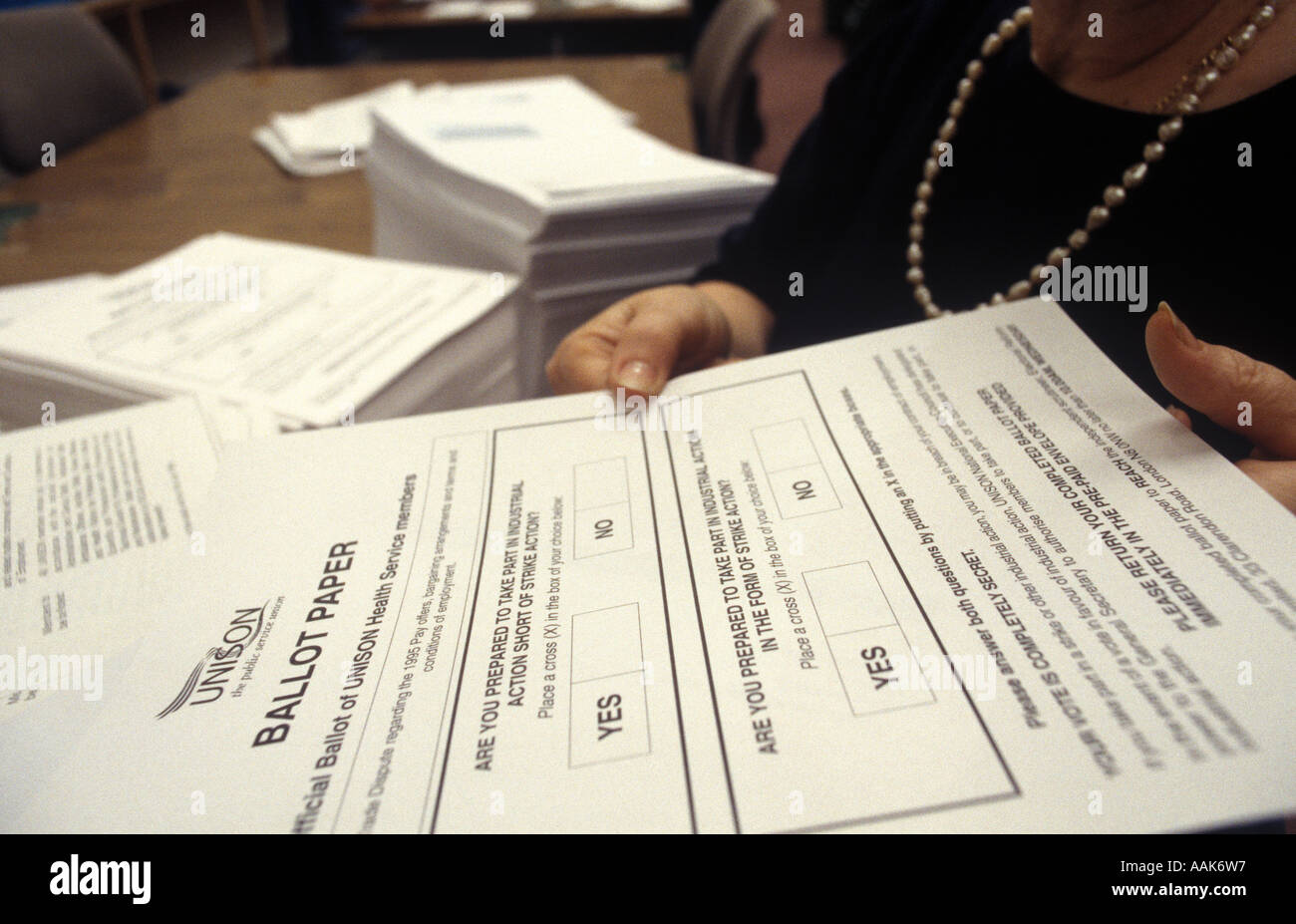 A woman prepares ballot papers for voting on Industrial action by members of the trade union UNISON, London, UK. - Stock Image
