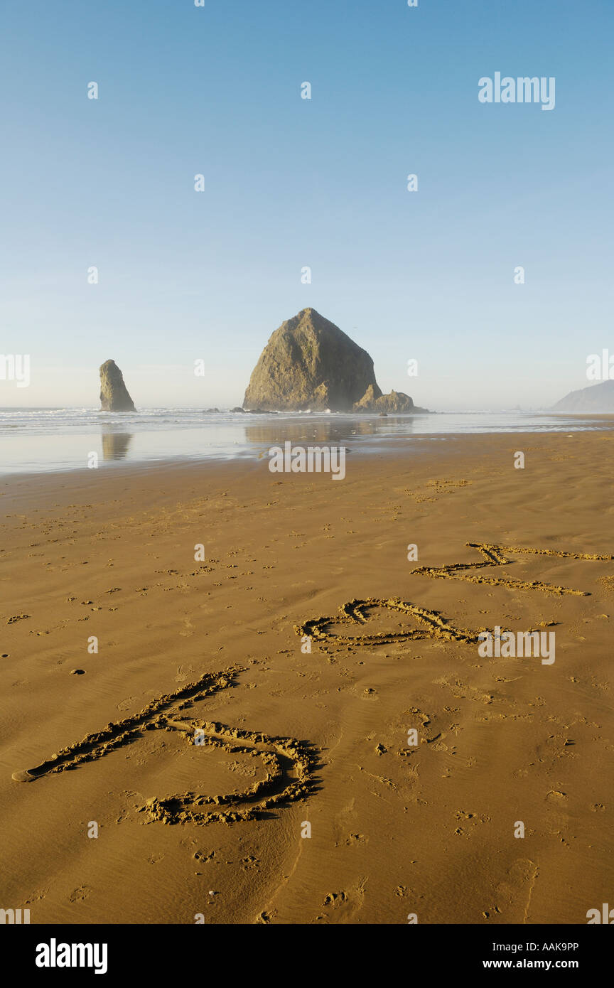 Haystack Rock at Cannon Beach with J loves M written in sand Oregon coast - Stock Image