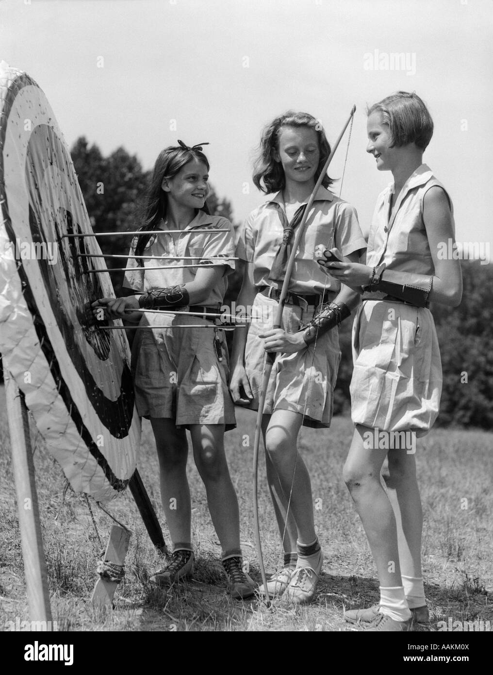 1930s 1940s THREE TEEN GIRLS STANDING BY ARCHERY TARGET BOWS ARROWS - Stock Image