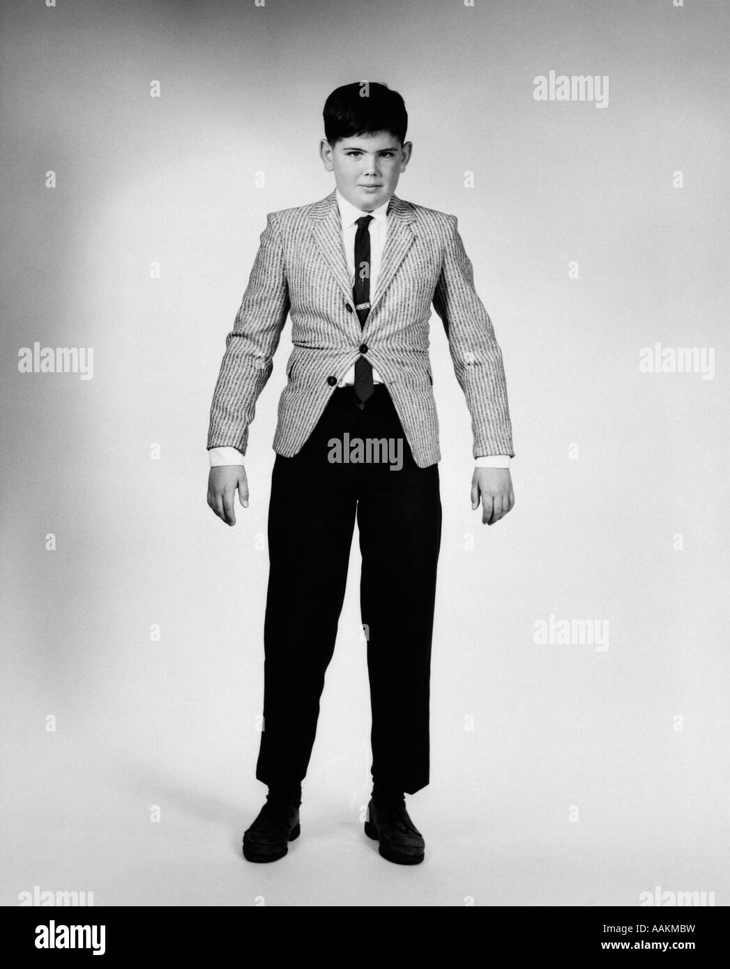 1950s 1960s OVERGROWN BOY IN TOO TIGHT SPORTS JACKET AND PANTS LOOKING AT CAMERA Stock Photo