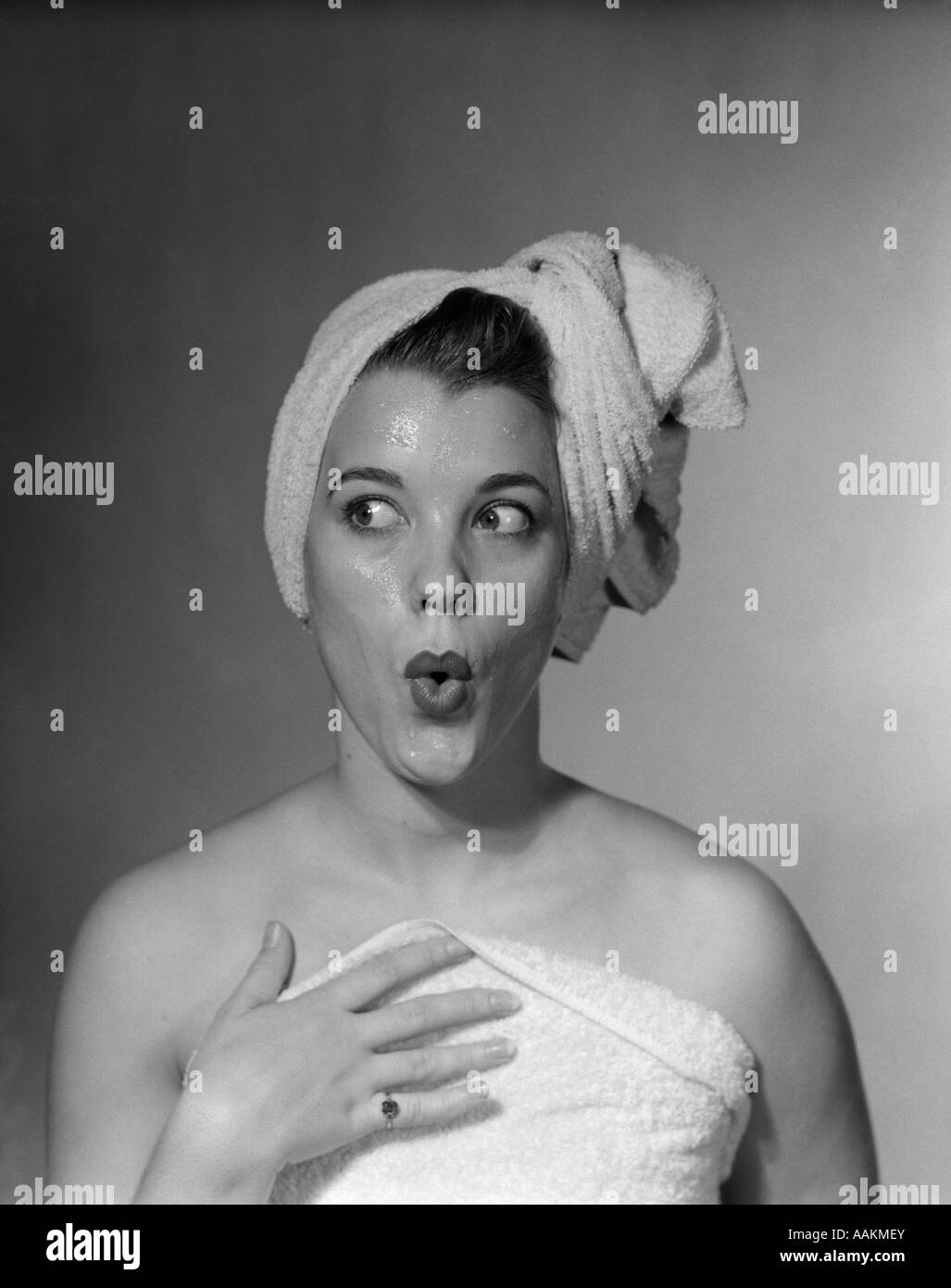 1950s WOMAN MAKING FUNNY FACE EXPRESSION WEARING TOWEL ON HEAD LOOKING OFF TO THE SIDE - Stock Image