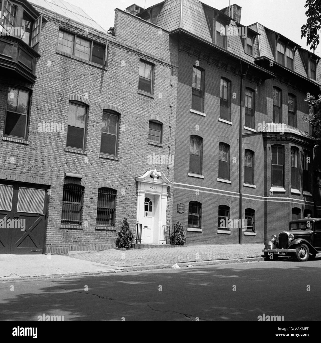 1920s WEST PHILADELPHIA PA BRICK RESIDENCE WITH CAR PARKED ON STREET - Stock Image