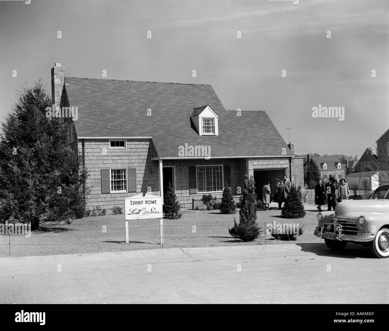 1940s 1950s LEVITTOWN MODEL HOME WITH SIGN OF LEVITT & SONS EXHIBIT HOME WITH PEOPLE MILLING ABOUT - Stock Image