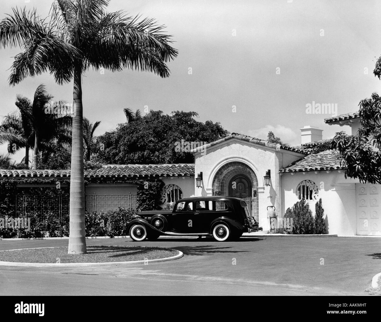 1930s CAR IN CIRCULAR DRIVEWAY OF TROPICAL STUCCO SPANISH STYLE HOME IN SUNSET ISLANDS MIAMI BEACH FLORIDA USA - Stock Image