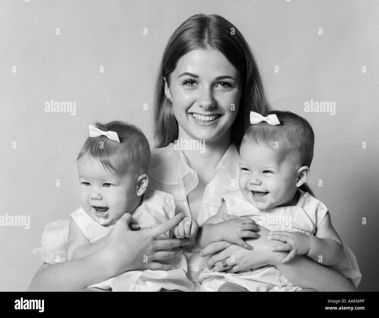 1970s PORTRAIT OF SMILING MOTHER WITH ARMS AROUND TWIN GIRLS WITH BOWS IN HAIR LOOKING AT CAMERA - Stock Image