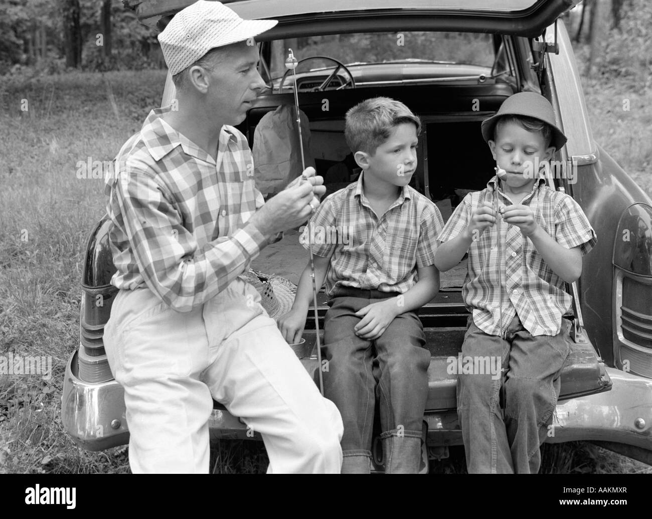1950s 1960s FATHER TWO YOUNG SONS WITH FISHING RODS BY CAR OUTDOOR Stock Photo