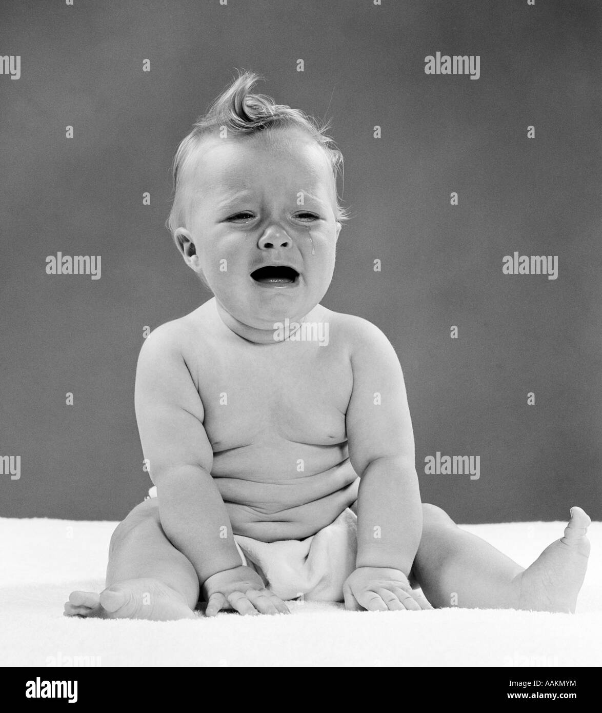 1950s CRYING BABY SEATED WITH DISTRESSED EXPRESSION & TEARS STREAMING OUT OF EYES - Stock Image