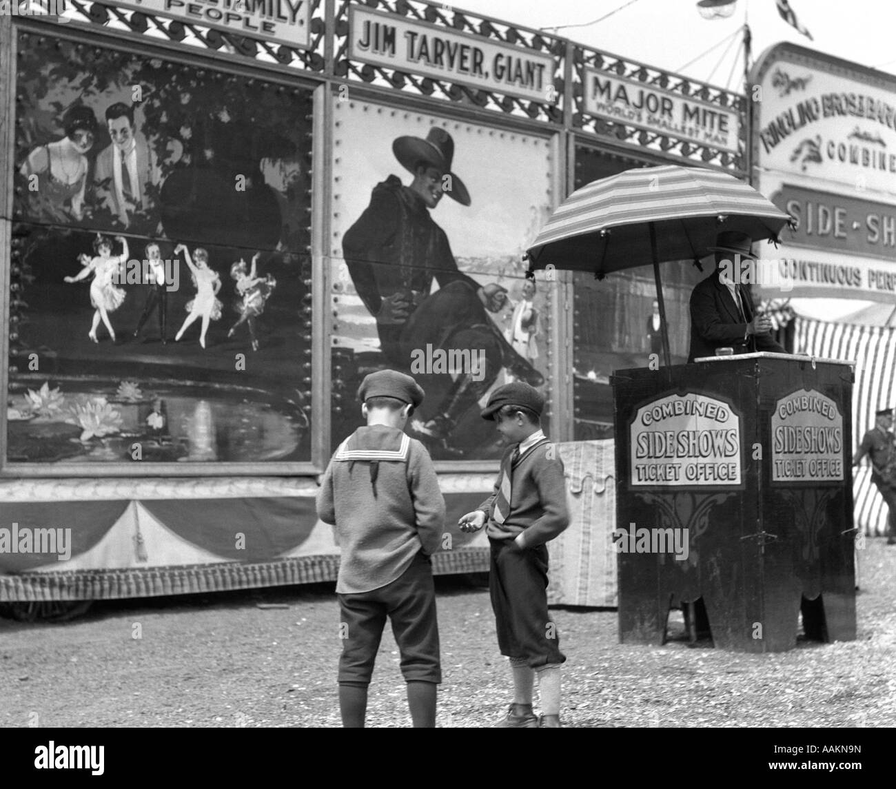 1920s BOYS COUNTING CHANGE FOR ENTRANCE TO CIRCUS SIDESHOW - Stock Image