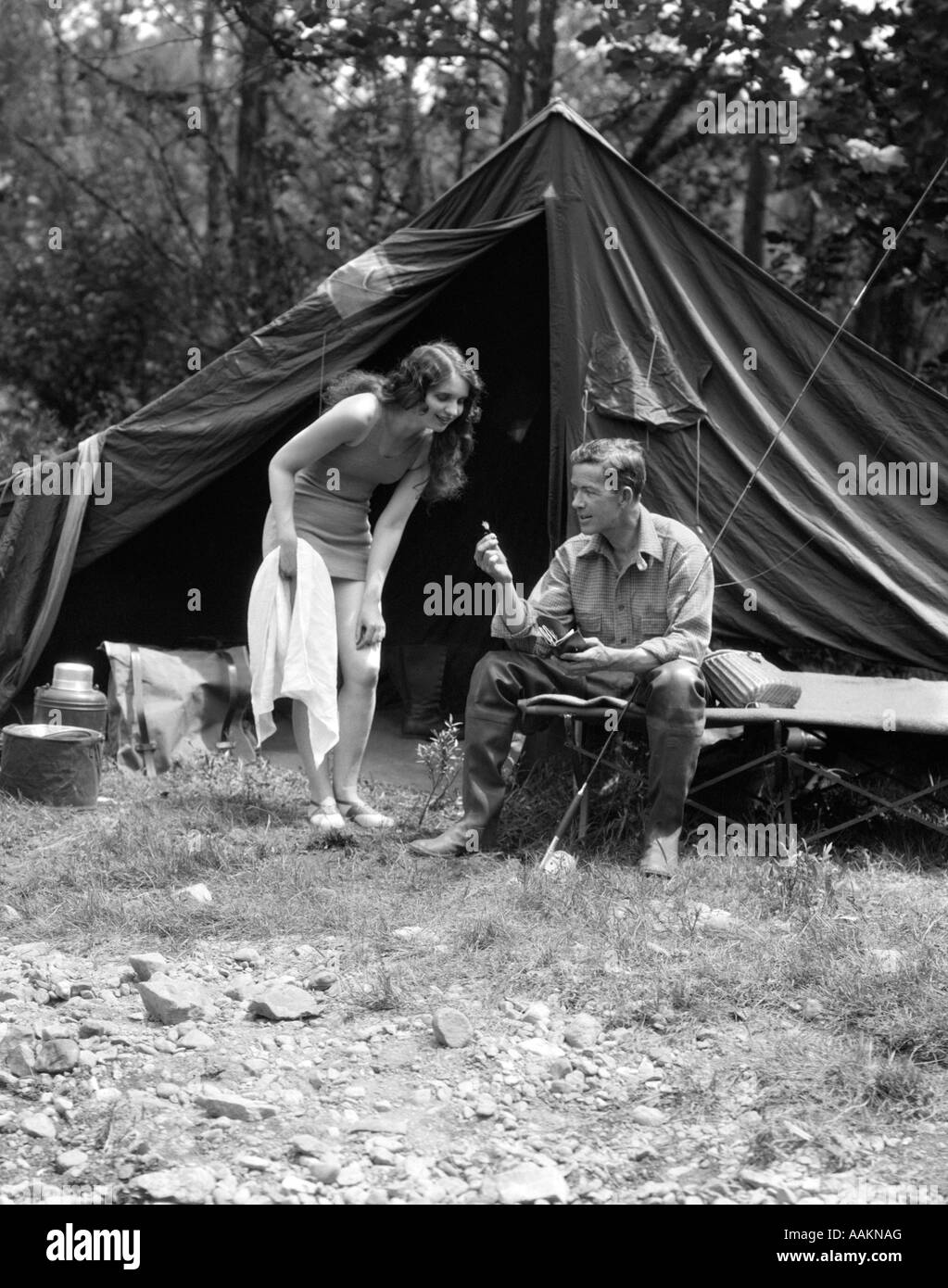 1920s camping couple man sitting by tent with fishing rod for Campsites with fishing