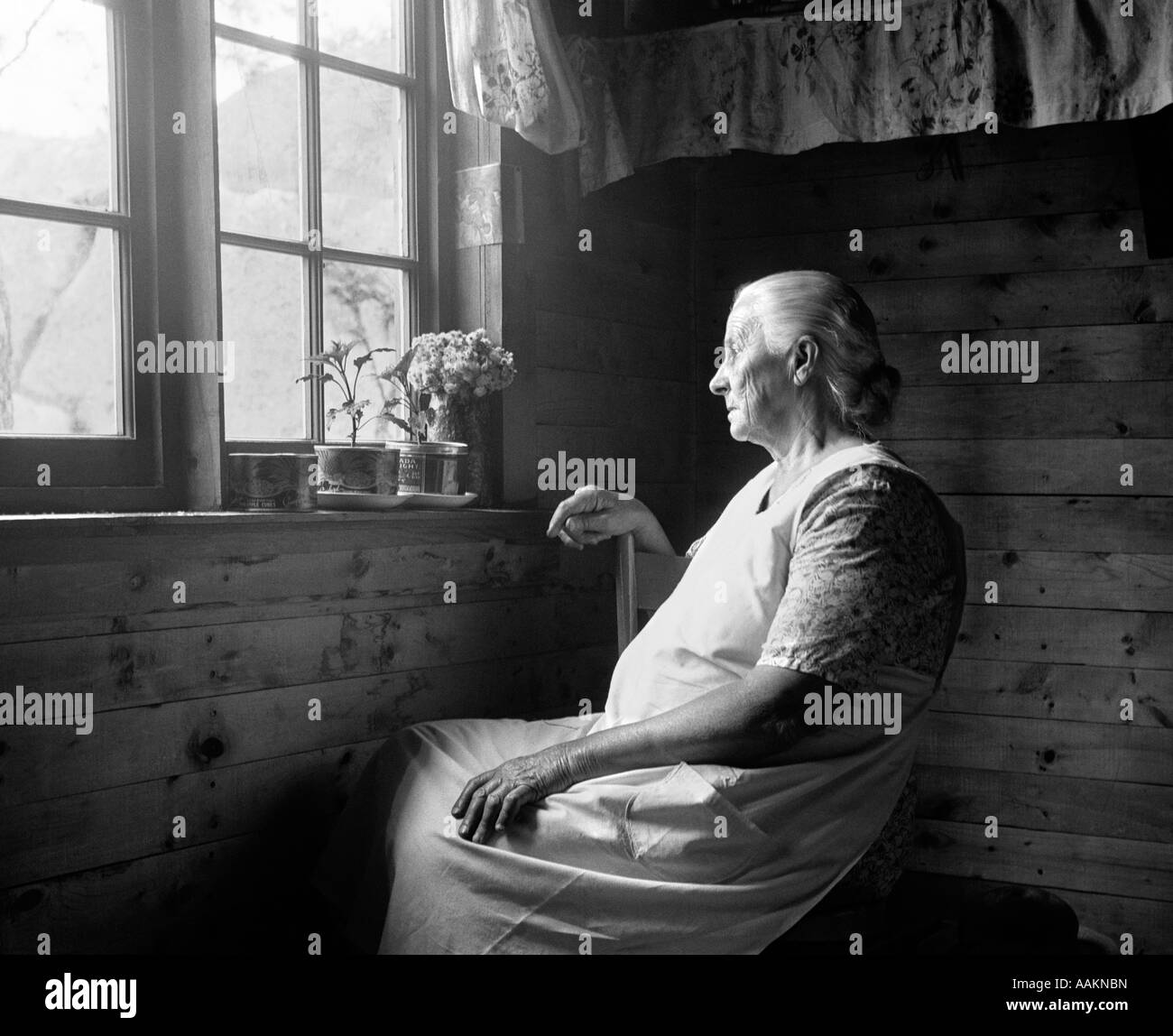 1950s Elderly Woman Seated In Dimly Lit Farmhouse With