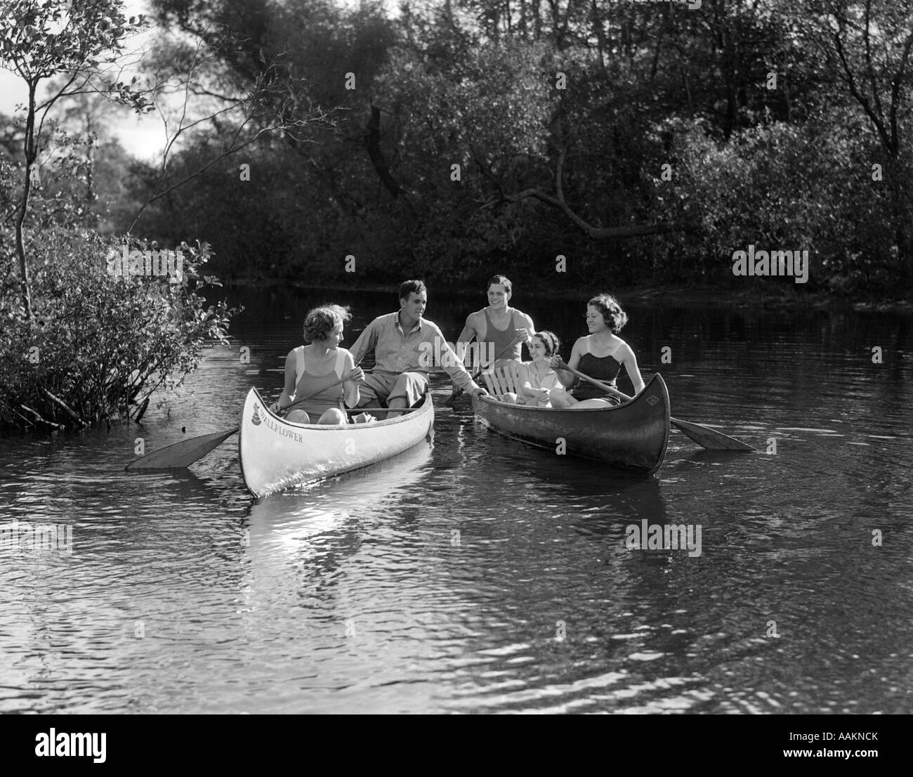 1930s SUMMERTIME GROUP OF FIVE YOUNG MEN & WOMEN IN TWO CANOES PADDLING DOWN A STREAM - Stock Image