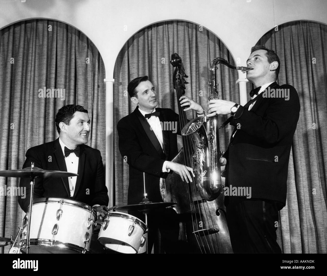 1950s THREE MEN IN TUXEDOS MUSICAL TRIO WITH DRUMS UPRIGHT BASE AND SAXOPHONE - Stock Image