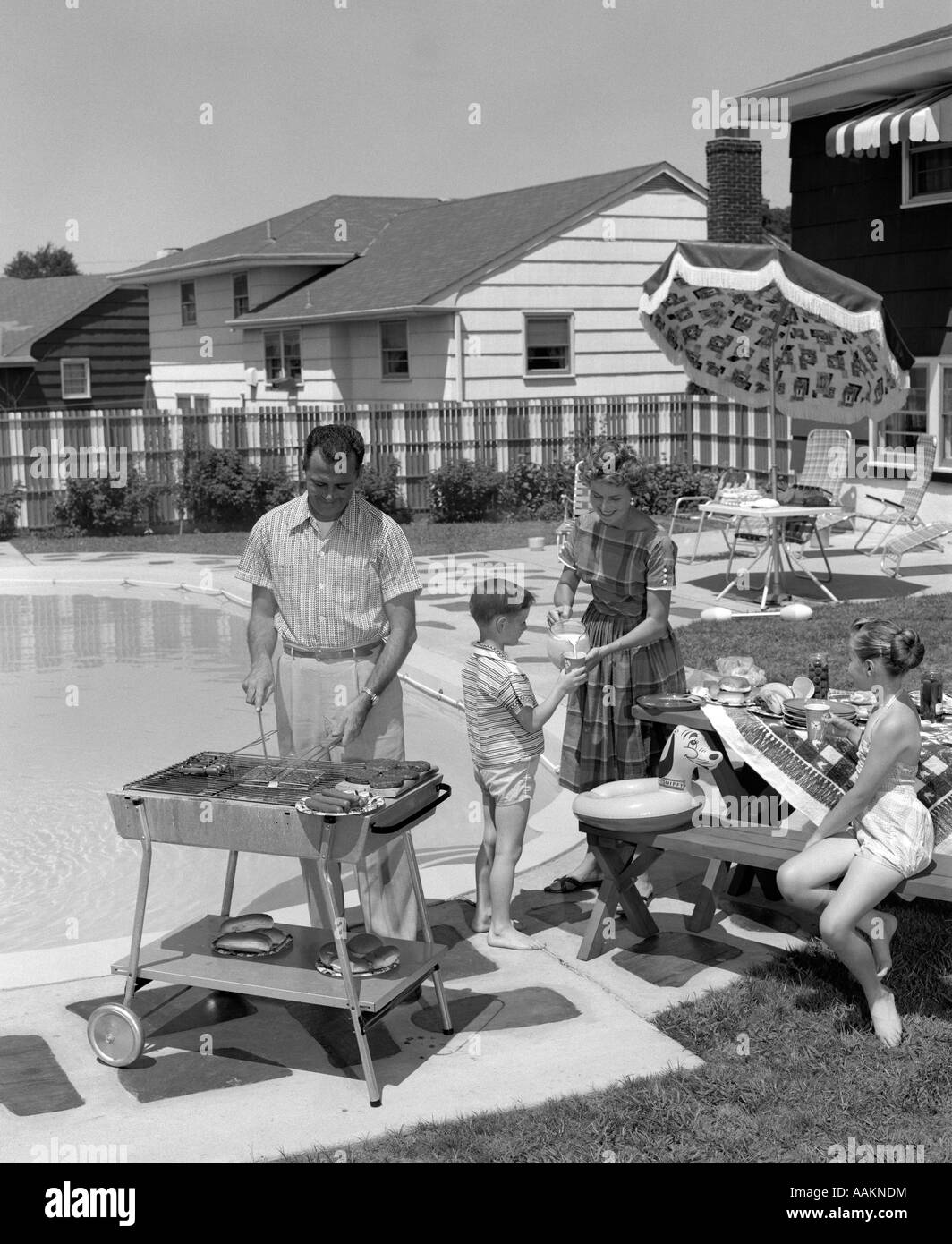 1950s FAMILY IN BACKYARD BESIDE POOL HAVING COOKOUT OF HOT DOGS & HAMBURGERS - Stock Image