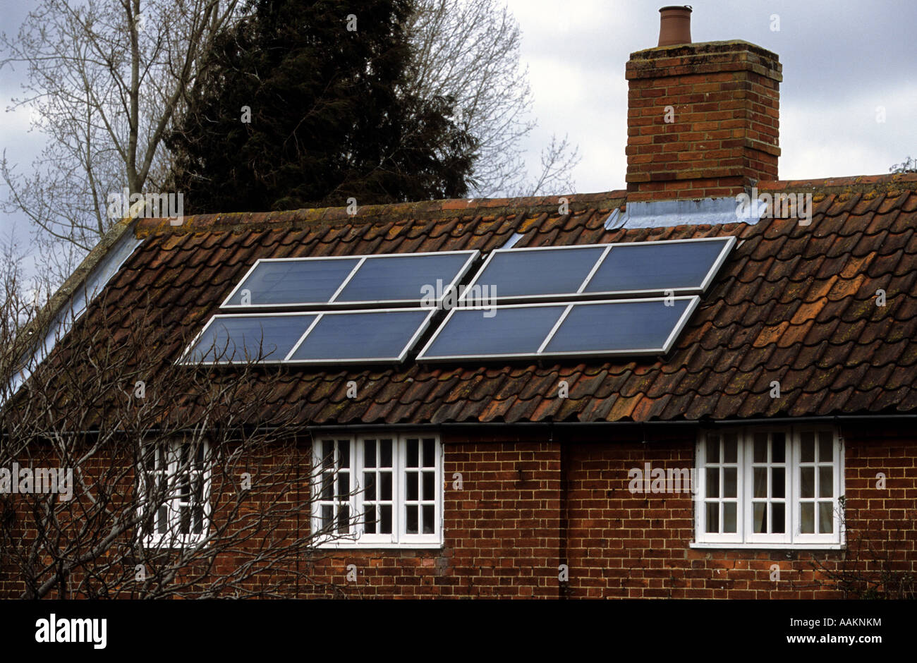 Photovoltaics or solar panels fitted to a roof of house to supply hot water, Snape, Suffolk, UK. - Stock Image