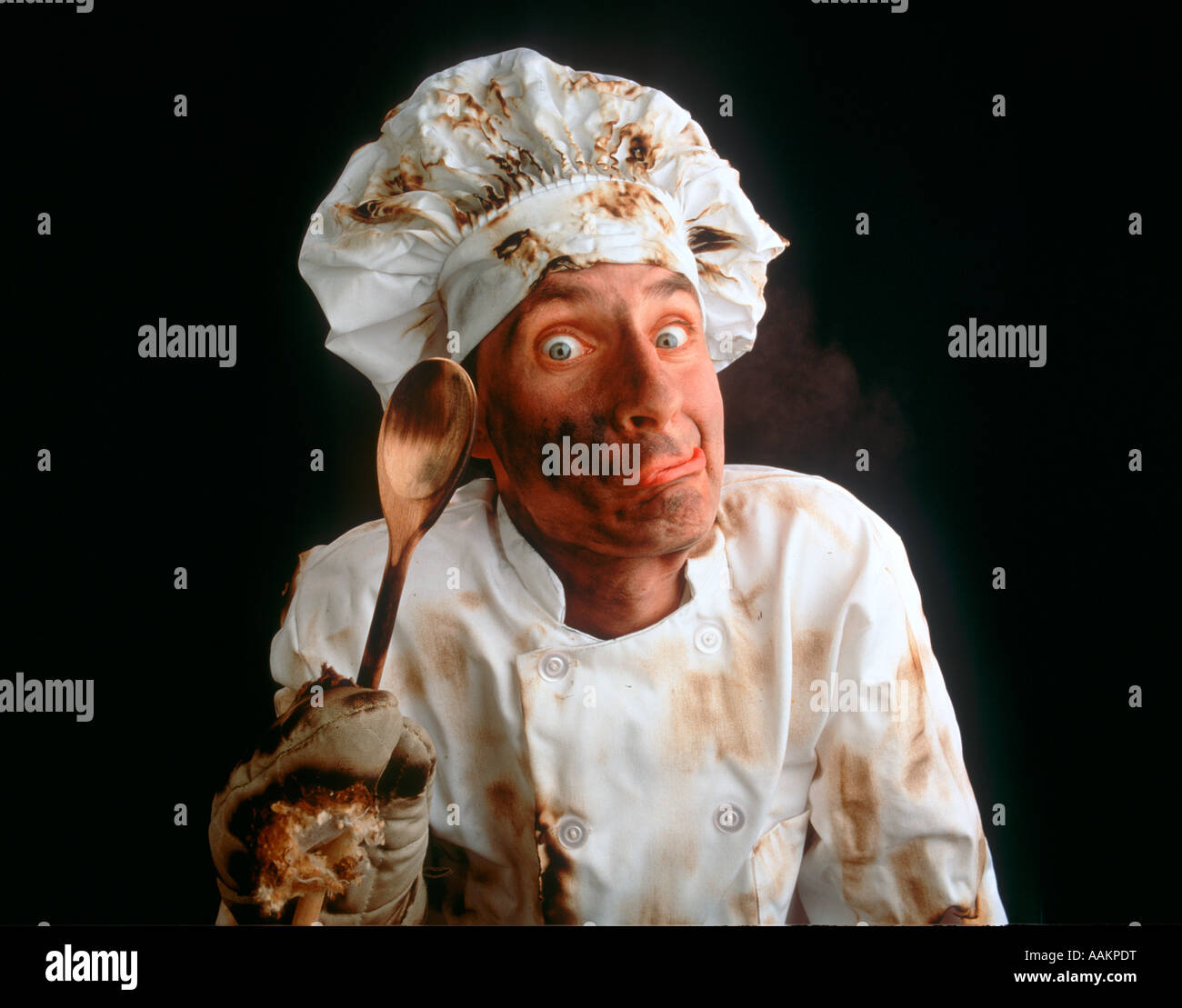 CHARACTER CHEF WITH FUNNY FACE HOLDING SPOON LOOKING DIRTY AND SLIGHTLY BURNED - Stock Image