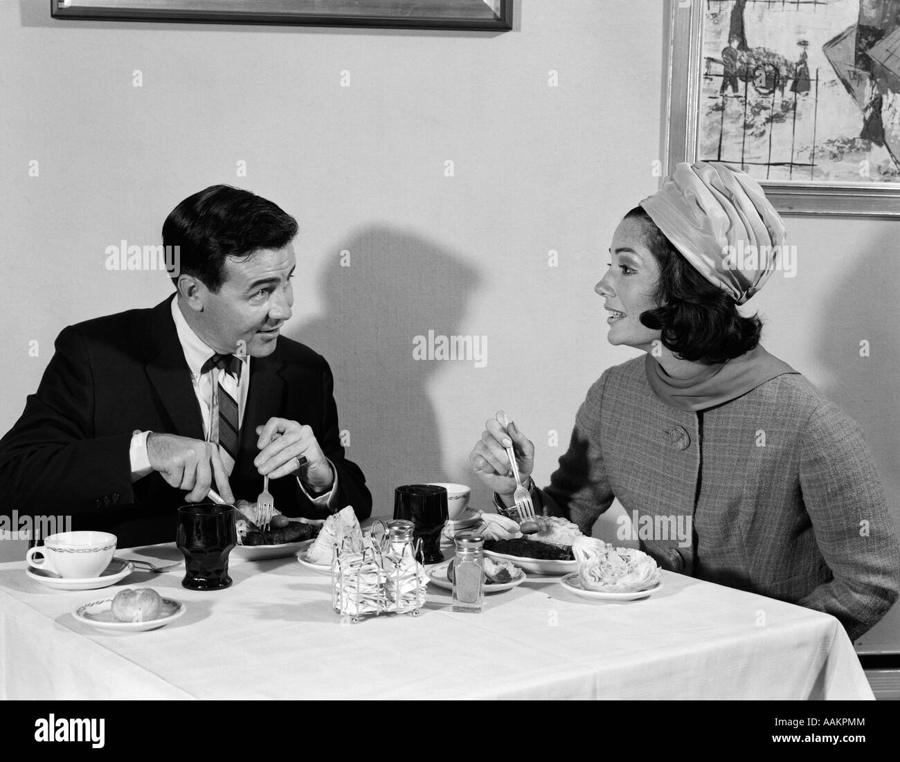 1960s COUPLE MAN WOMAN EATING MEAL IN RESTAURANT WOMAN WEARS TURBAN STYLE HAT - Stock Image