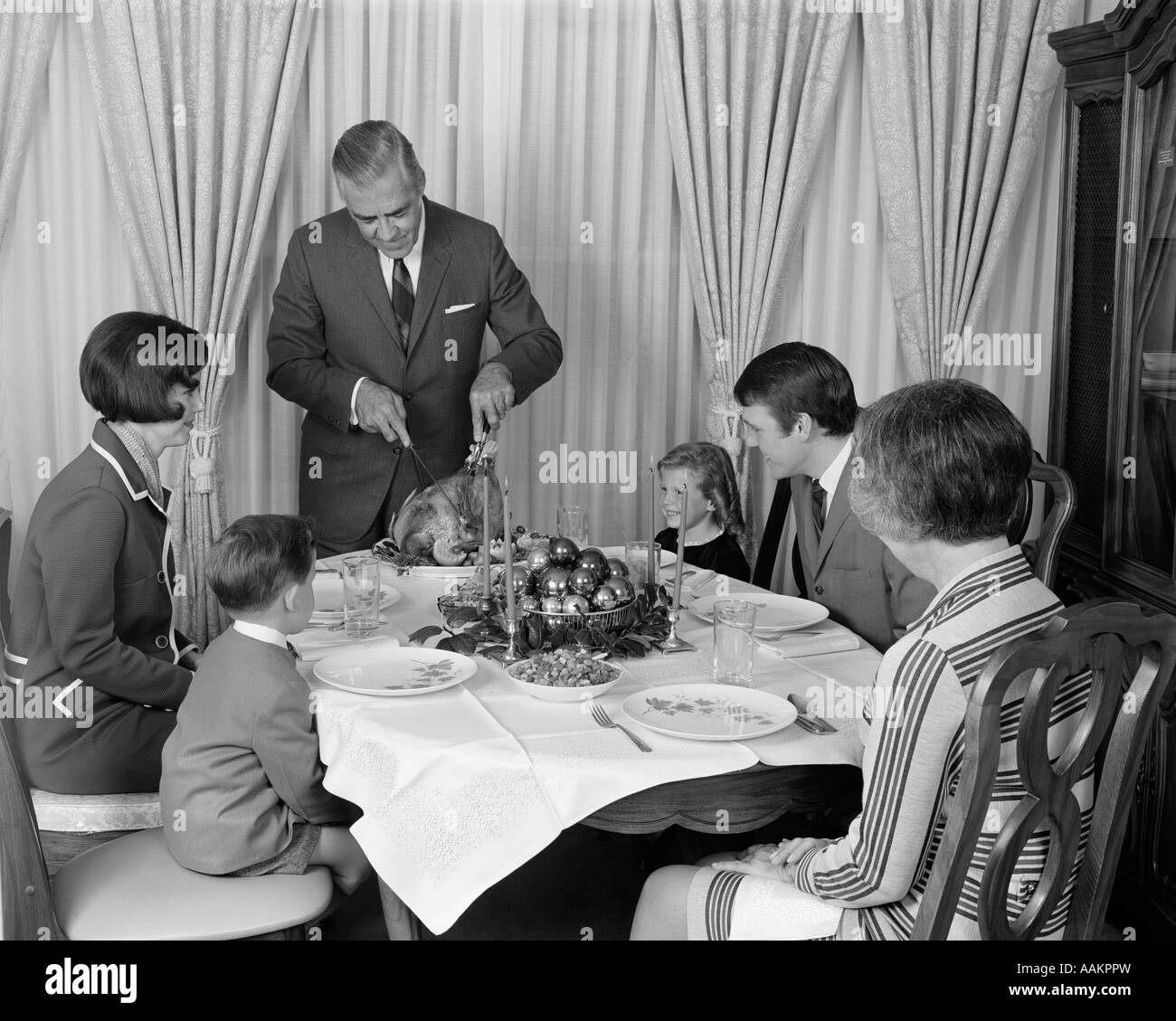 1960s GRANDFATHER STANDING CARVING THANKSGIVING TURKEY SURROUNDED BY THREE GENERATION FAMILY - Stock Image