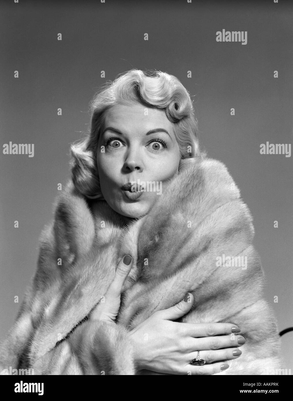 1950s WOMAN WRAPPED IN FUR STOLE MAKING FUNNY FACIAL EXPRESSION LOOKING AT CAMERA - Stock Image