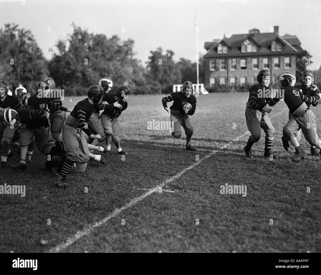 1930s BOYS SCHOOL FOOTBALL TEAM BOY RUNNING WITH BALL CENTER - Stock Image