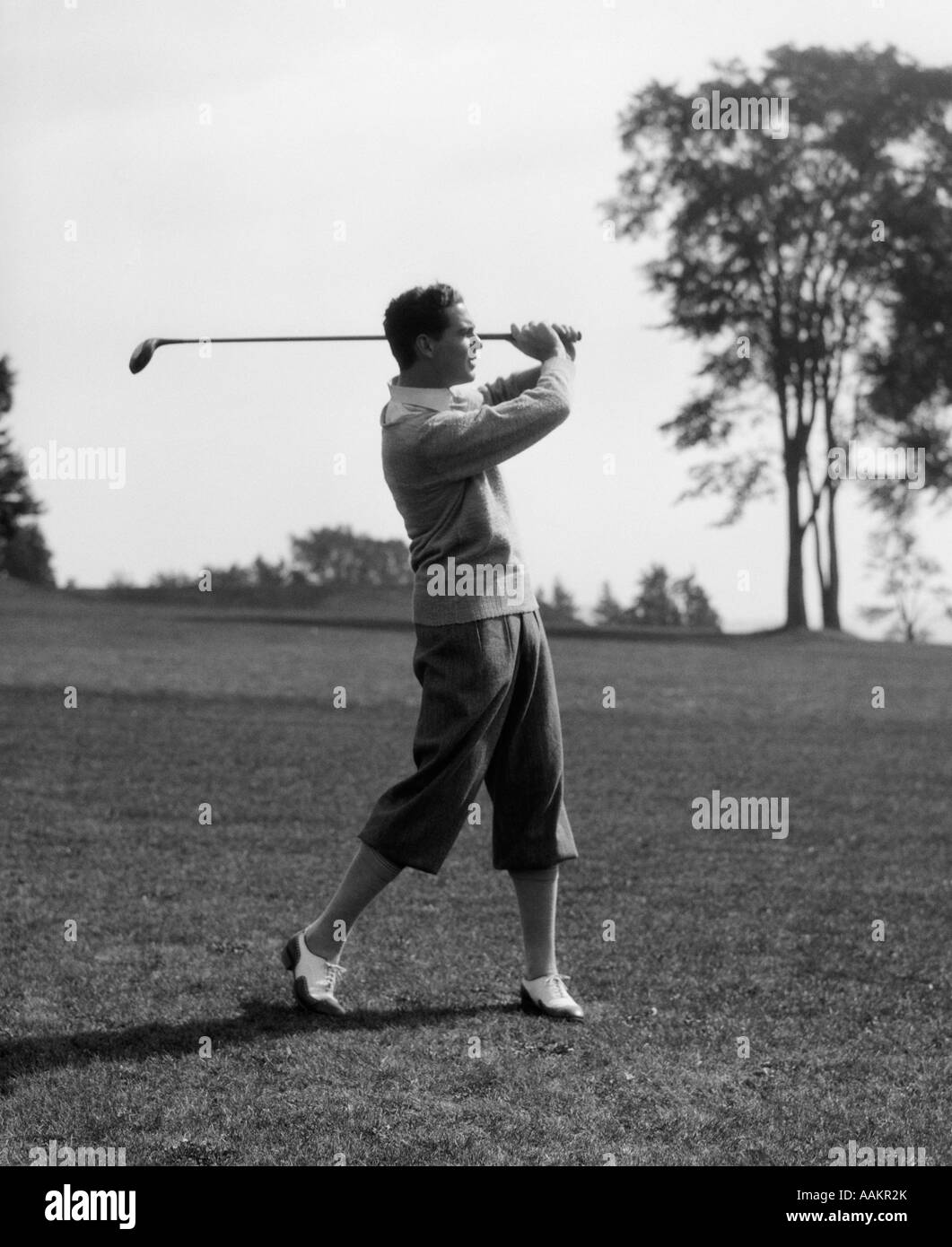 1930s GOLFER IN KNICKERS WITH CLUB IN AIR - Stock Image