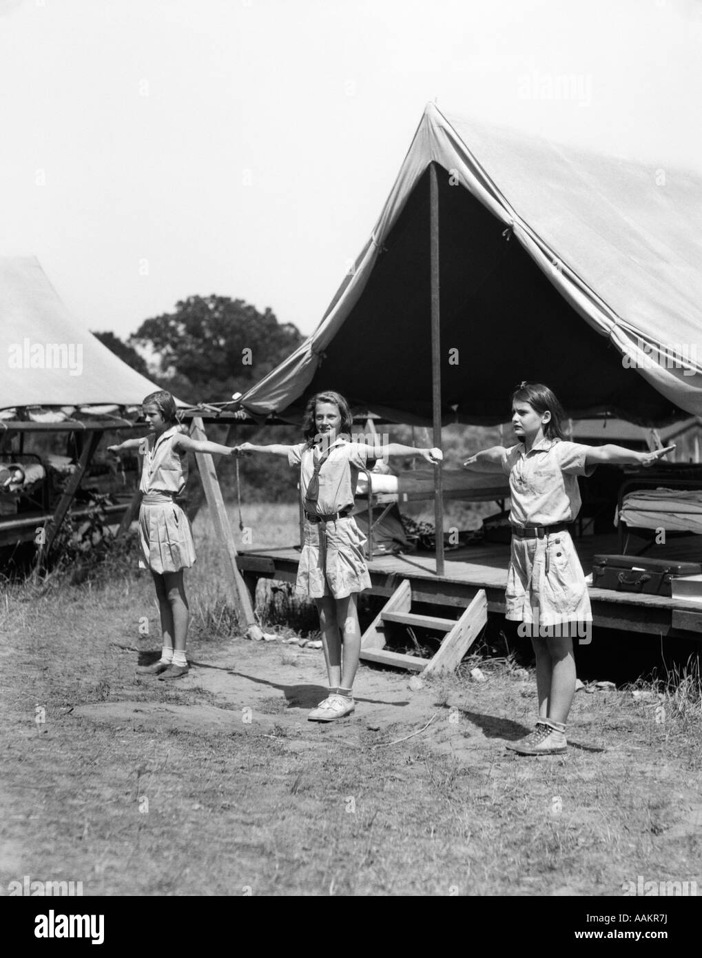 1930s THREE TEEN GIRLS DOING EXERCISE IN A ROW WITH ARMS EXTENDED BY TENT SUMMER CAMP - Stock Image