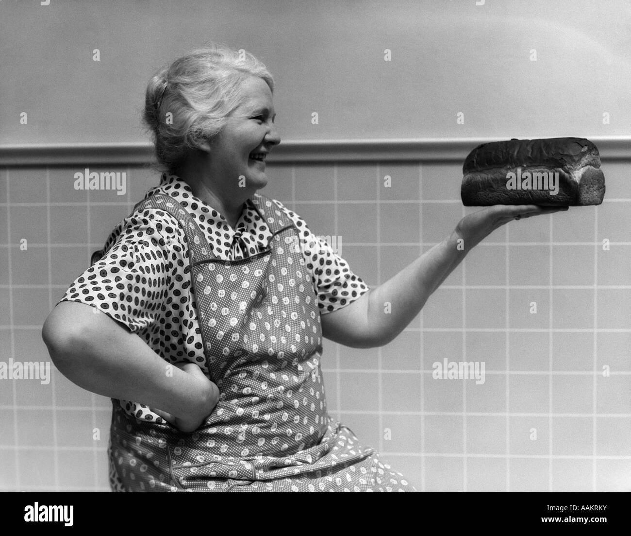 1930s 1940s GRANDMOTHER IN APRON ADMIRING LOAF OF FRESHLY BAKED BREAD - Stock Image