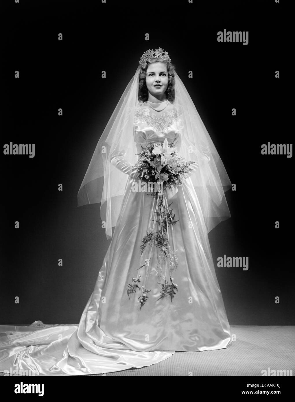 1940s FULL LENGTH PORTRAIT OF BRIDE IN WEDDING DRESS LOOKING AT CAMERA Stock Photo