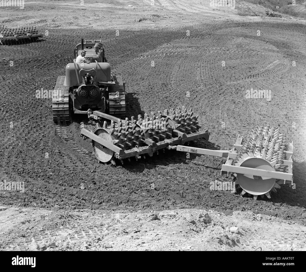 1960s MAN OPERATING GRADING MACHINE IN SOIL CONSTRUCTION SITE HEAVY MACHINERY ATTACHMENT ROLLER WITH SPIKES - Stock Image